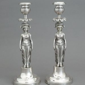 A PAIR OF SILVER CANDLESTICKS SHAPED AS CARYATIDS